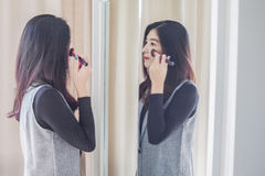 Asian portrait beautiful woman making make-up with brush on face Stock Photography