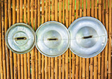 Asian Pot's lids. 3 Asian Pot's lids hanging by 1 string on a bamboo wall Royalty Free Stock Photos
