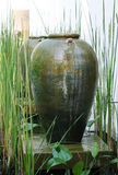 Asian pottery. Large Asian pottery garden decoration surrounded by greenery Stock Photo