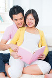 Asian pregnant couple reading book Stock Images