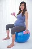 Asian pregnant woman doing exercise with swiss ball, smiling Royalty Free Stock Photo