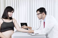 Asian pregnant woman having a consultation with a gynecologist stock photos