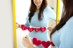 Asian pregnant woman with heart shape accessories on her tummy Stock Images