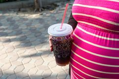 Asian pregnant woman holding a cup of softdrink Stock Photos