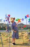 Asian pregnant woman in the middle of colorful pinwheel royalty free stock image