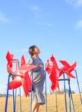 Asian pregnant woman in the middle of red pinwheel royalty free stock photo