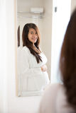 Asian pregnant woman posing in front of a mirror, smiling happil Stock Image