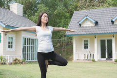 asian pregnant woman practicing yoga on green grass in front of Royalty Free Stock Photography