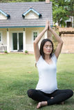 asian pregnant woman practicing yoga on green grass in front of Stock Photo
