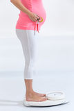 Asian pregnant woman standing on weight scale Royalty Free Stock Image