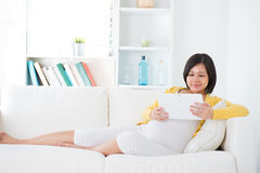Asian  pregnant woman using tablet computer Royalty Free Stock Photos