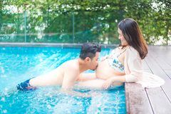 Asian pregnant woman with big belly. Asian pregnant women with big belly. Relax and exercise at swimming pool with husband stock photos