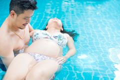 Asian pregnant woman with big belly. Relax and exercise at swimming pool. Asian pregnant women with big belly. Relax and exercise at swimming pool with husband stock photography