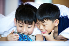 Asian Preschool boys playing on smartphone together. Rest on bed stock photos