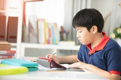 Asian preteens doing your homework with tablet. Asian preteens doing your homework with tablet computer with serious face Royalty Free Stock Image