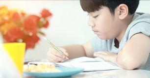 Asian preteens doing your homework with tablet. Asian preteens doing your homework with tablet computer with serious face Royalty Free Stock Photo