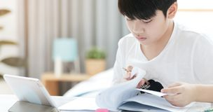 Asian preteens doing your homework with tablet. Asian preteens doing your homework with tablet computer with serious face Stock Photos