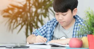 Asian preteens doing your homework with tablet. Asian preteens doing your homework with tablet computer with serious face Stock Photography