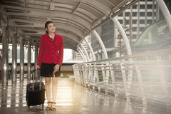 Asian pretty business woman standing with luggage. Stock Image