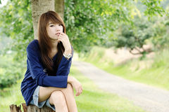 Asian pretty face girl. Sitting next the country road Royalty Free Stock Photography