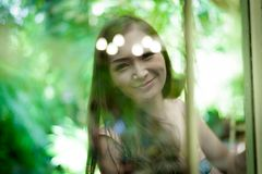 Asian pretty girl has relaxing behind blurred mirror with happy. And smiling at Little Tree Garden cafe, Nakhon Pathom province, Thailand in the morning stock photo