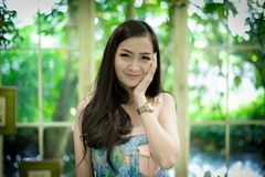 Asian pretty girl has relaxing with happy and smiling at Little. Tree Garden cafe, Nakhon Pathom province, Thailand in the morning. background beautiful beauty stock photography