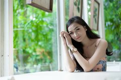 Asian pretty girl has relaxing with happy and smiling at Little. Tree Garden cafe, Nakhon Pathom province, Thailand in the morning. background beautiful beauty stock images