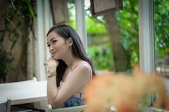Asian pretty girl has relaxing with happy and smiling at Little Tree Garden cafe, Nakhon Pathom province, Thailand in the morning. Background beautiful beauty royalty free stock photos