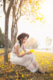 Asian pretty girl surrounded by the yellow flowers in summer.  Royalty Free Stock Photo