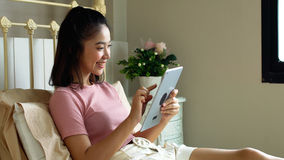 Asian pretty girl using tablet in the bedroom Royalty Free Stock Images