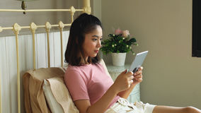 Asian pretty girl using tablet in the bedroom Stock Photography