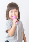 Little cute asian girl singing holding microphone over white background. Stock Photos