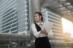 Asian Pretty woman in black dress writing document stand on pole. Royalty Free Stock Image
