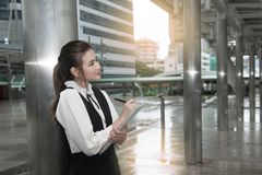 Asian Pretty woman in black dress writing document stand on pole. Stock Photography