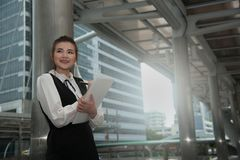 Asian Pretty woman in black dress writing document stand on pole. Royalty Free Stock Photography