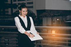 Asian Pretty woman in black dress writing document standing crossing bridge. Stock Photography