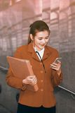 Asian Pretty woman holding document and use smart phone. Stock Image
