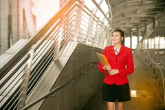 Asian Pretty woman in red suit holding document walking. Stock Photography