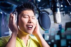 Asian male singer producing song in recording studio. Asian professional musician recording new song or album CD in studio Royalty Free Stock Photos