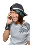Asian punker calling by cell phone. Asian teenager with cap and cell phone, calling and smiling, and with punk one-sided colored long hair. Emo and friendly royalty free stock photo
