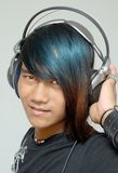 Asian punker portrait with headphones. Asian teenager portrait with headphones enjoying music, and with punk one-sided colored long hair. Emo and macho punker royalty free stock image