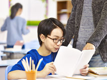 Asian pupil getting help from teacher. Asian elementary schoolboy getting help from teacher or tutor in classroom at school Stock Photography
