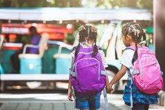 Asian pupil kids with backpack holding hand and going to school royalty free stock photography