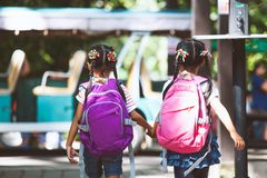 Asian pupil kids with backpack holding hand and going to school stock images