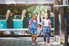 Asian pupil kids with backpack holding hand and going to school royalty free stock photo