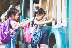 Asian pupil kids with backpack holding hand and going to school. With school bus together. Back to school concept stock photo