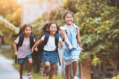Asian pupil kids with backpack running. Back to school. Asian pupil kids with backpack running and going to school together with fun and happiness in vintage stock images