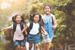 Asian pupil kids with backpack running. Back to school. Asian pupil kids with backpack running and going to school together with fun and happiness in vintage stock photography