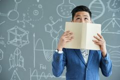Asian Pupil with Textbook. Waist-up portrait of Asian pupil covering his face with textbook and looking upwards while standing against blackboard with Royalty Free Stock Photo