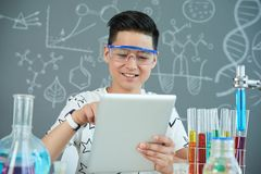 Asian Pupil Wrapped up in Work. Cheerful Asian pupil wearing protective goggles using digital tablet while finishing school project at modern chemistry class Stock Photos